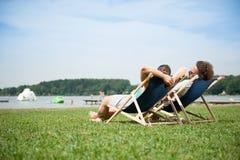Paare, die in der Sonne sich entspannen Lizenzfreie Stockbilder
