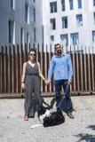 Paare, die in der Stadt mit Hund am asunny Tag stehen lizenzfreies stockbild