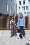 Paare, die in der Stadt mit Hund am asunny Tag stehen lizenzfreie stockfotos