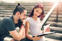 Paare, die in der Treppe am Universitätsgelände sitzen Lizenzfreie Stockbilder