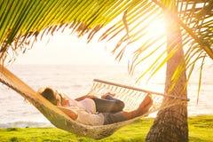 Paare, die in der tropischen Hängematte sich entspannen Stockfoto