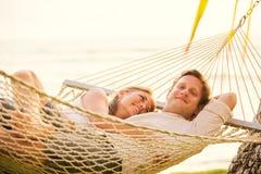 Paare, die in der tropischen Hängematte sich entspannen Stockfotografie