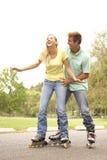 Paare, die in der Zeile Rochen im Park tragen lizenzfreies stockbild