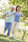 Paare, die draußen in das Parklächeln laufen Lizenzfreies Stockfoto