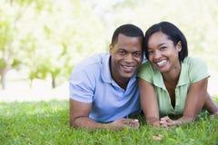 Paare, die draußen lächelnd liegen Stockbild