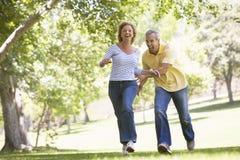Paare, die draußen in Park und das Lächeln laufen Stockfotografie