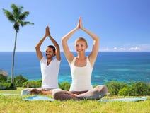 Paare, die draußen Yoga in der Lotoshaltung tun Lizenzfreie Stockbilder