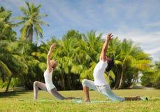 Paare, die draußen Yoga in der niedrigen Laufleinenhaltung machen Stockfotos