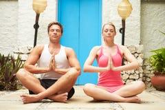 Paare, die draußen am Gesundheits-Badekurort meditieren Lizenzfreies Stockbild