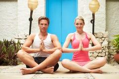 Paare, die draußen am Gesundheits-Badekurort meditieren Lizenzfreie Stockfotos