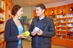 Paare, die Drogen in der Apotheke vergleichen lizenzfreies stockbild