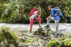 Paare, die durch den Fluss wandern Lizenzfreie Stockfotografie