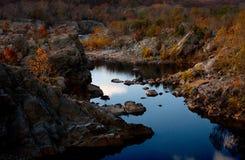Paare, die durch Fluss im Herbst sitzen Stockfoto