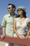 Paare, die durch Geländer im Freien umfassen Stockbilder