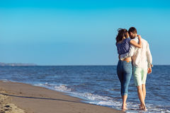 Paare, die durch Heron gehen Junge glückliche zwischen verschiedenen Rassen Paare, die auf Strand gehen Stockbilder