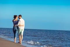 Paare, die durch Heron gehen Junge glückliche zwischen verschiedenen Rassen Paare, die auf Strand gehen Lizenzfreie Stockfotografie