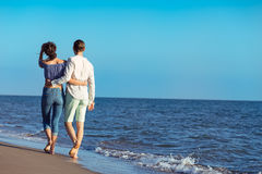 Paare, die durch Heron gehen Junge glückliche zwischen verschiedenen Rassen Paare, die auf Strand gehen Lizenzfreie Stockbilder