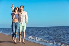 Paare, die durch Heron gehen Junge glückliche zwischen verschiedenen Rassen Paare, die auf Strand gehen Lizenzfreies Stockbild