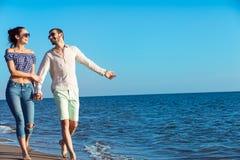 Paare, die durch Heron gehen Junge glückliche zwischen verschiedenen Rassen Paare, die auf Strand gehen Stockfotografie