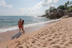 Paare, die durch Heron gehen Junges glückliches Paar, das auf dem lächelnden Halten des Strandes um einander geht Lizenzfreie Stockbilder