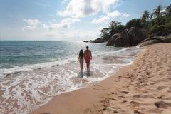 Paare, die durch Heron gehen Junges glückliches Paar, das auf dem lächelnden Halten des Strandes um einander geht Stockbilder