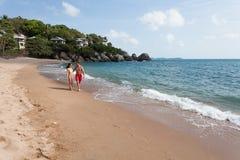 Paare, die durch Heron gehen Junges glückliches Paar, das auf dem lächelnden Halten des Strandes um einander geht Stockfotografie