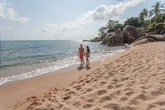 Paare, die durch Heron gehen Junges glückliches Paar, das auf dem lächelnden Halten des Strandes um einander geht Lizenzfreies Stockfoto