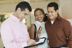 Paare, die durch Kreditkarte im Möbelgeschäft zahlen Lizenzfreies Stockbild