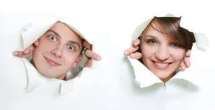 Paare, die durch Loch im Papier lugen Stockfotos