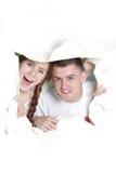Paare, die durch Loch im Papier lugen Stockbild