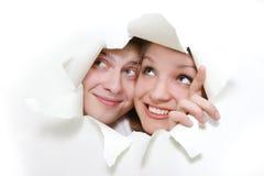 Paare, die durch Loch im Weißbuch lugen Stockfotografie