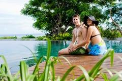 Paare, die durch Pool sich entspannen Stockfoto