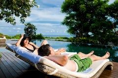 Paare, die durch Pool sich entspannen Stockbilder