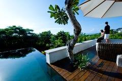 Paare, die durch Pool sich entspannen Lizenzfreie Stockbilder