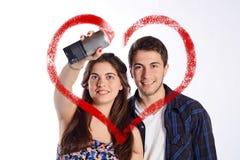Paare, die ein Herz mit Aerosoldose zeichnen Stockbild