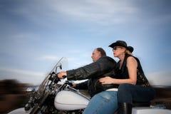 Paare, die ein Motorrad reiten lizenzfreie stockbilder