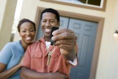 Paare, die ein Paar Haus-Schlüssel zeigen Lizenzfreie Stockbilder