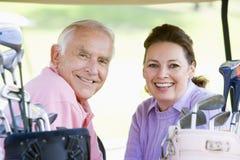 Paare, die ein Spiel des Golfs genießen Stockbilder