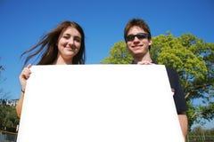 Paare, die ein unbelegtes Zeichen anhalten Stockfoto