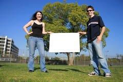 Paare, die ein unbelegtes Zeichen anhalten lizenzfreies stockbild