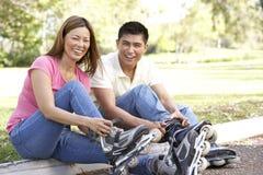 Paare, die ein in Zeile Rochen im Park sich setzen Stockfoto