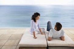 Paare, die einander bei der Entspannung auf Sunbeds betrachten Stockfotografie