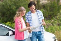 Paare, die eine Karte betrachten Lizenzfreie Stockfotografie