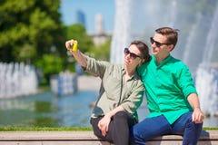 Paare, die einem selfie Hintergrund den Brunnen nehmen Junger Mann, der Foto von der Frau auf der Straße Spaß herein lachend und  Lizenzfreies Stockfoto