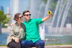 Paare, die einem selfie Hintergrund den Brunnen nehmen Junger Mann, der Foto von der Frau auf der Straße Spaß herein lachend und  Stockfotografie