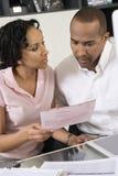 Paare, die einen Bill besprechen Stockbild