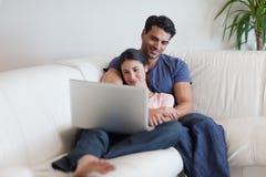 Paare, die einen Film beim Essen des Popcorns überwachen Lizenzfreies Stockfoto