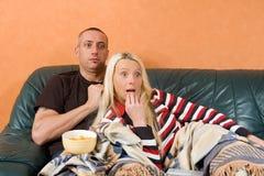 Paare, die einen furchtsamen Film überwachen stockbilder