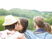 Paare, die einen Kuss beim Sitzen mit Freunden teilen Lizenzfreies Stockfoto