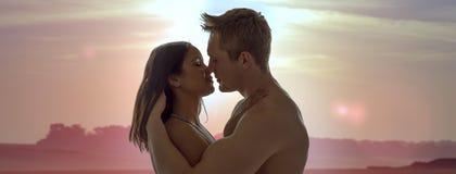 Paare, die einen romantischen Sonnenuntergangkuß genießen Lizenzfreie Stockfotografie
